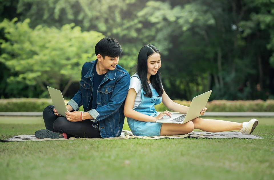 twee mensen met laptop op het gras